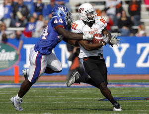 photo - Oklahoma State's Justin Blackmon (81) tries to get by Kansas' Olaitan Oguntodu (44) during the college football game between Oklahoma State (OSU) and Kansas (KU), Saturday, Nov. 20, 2010 at Memorial Stadium in Lawrence, Kans. Photo by Sarah Phipps, The Oklahoman