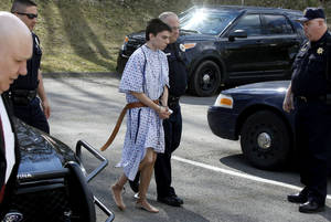 Photo - Alex Hribal, the suspect in the multiple stabbings at the Franklin Regional High School in Murrysville, Pa., is escorted by police to a district magistrate to be arraigned on Wednesday, April 9, 2014, in Export, Pa. Authorities say Hribal has been charged after allegedly stabbing and slashing at least 19 people including students in the crowded halls of his suburban Pittsburgh high school Wednesday. (AP Photo/Keith Srakocic)