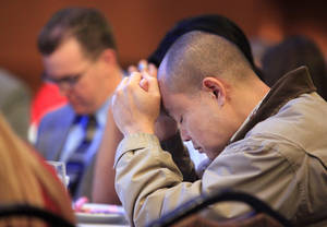 Photo - Brad Riebe, right, of Oklahoma City,  bows his head in prayer at the 2011 CBMC Metro Prayer Breakfast in downtown Oklahoma City. The 2013 event is set for March 26 at the Cox Convention Center.   <strong>PAUL B. SOUTHERLAND - PAUL B. SOUTHERLAND</strong>