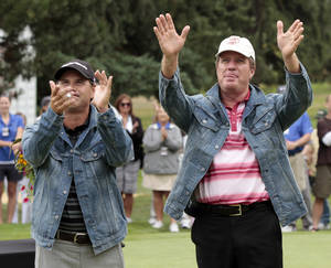 Photo - Scott McCarron , left, and teammate Steve Elkington, right, acknowledge the crowd after winning the Umpqua Challenge golf tournament in Portland, Ore. Tuesday, Aug. 30, 2011.  The pair won the tournament with a two-day score of 24-under-par 120.(AP Photo/Don Ryan)