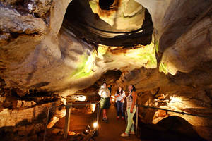 Photo - Kim LaFon, a historical interpreter, from left,  leads a tour of Alabaster Cavern with Denise and Chris Gutierrez of Albuquerque, N.M. and Christabell Gutierrez of Alva.  <strong>David McDaniel - The Oklahoman</strong>