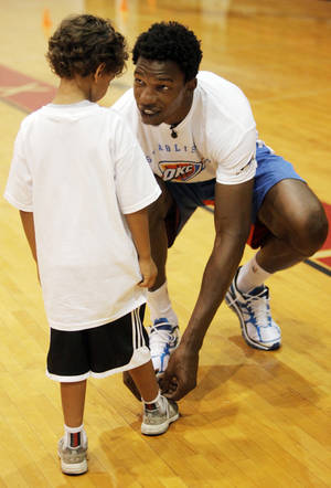 Photo - Hasheem Thabeet, center for the Oklahoma City Thunder, ties the shoes of Jay Kakani, 6 of Oklahoma City, at the Thunder basketball camp at Carl Albert High School in Midwest City on June 25, 2013. Photo by KT KING, The Oklahoman