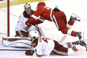 Photo - Detroit Red Wings center Damien Brunner, of Switzerland, trips on Phoenix Coyotes defenseman David Schlemko (6) into goalie Mike Smith (41) in the third period of an NHL hockey game in Detroit, Monday, April 22, 2013. Detroit won 4-0. (AP Photo/Paul Sancya)