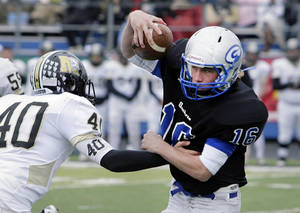 photo - McAlester&#039;s Austin Harvanek is blown past by Guthrie quarterback Bryan Dutton in the 2nd half of their 5A semifinal game at Sapulpa, OK, Nov. 26, 2011. MICHAEL WYKE/Tulsa World 