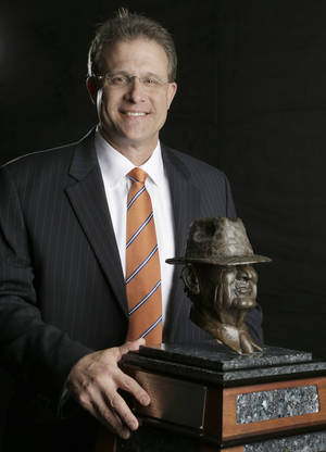 "Photo - Auburn coach Gus Malzhan, a finalist for the Paul ""Bear"" Bryant college coach of the year award, poses with the trophy Wednesday, Jan. 15, 2014, in Houston. (AP Photo/Pat Sullivan)"