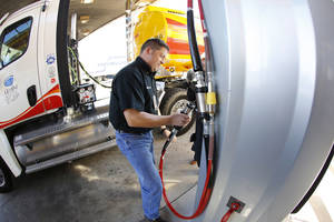 Photo - Gemini Motor Transport driver Robert Felts demonstrates how to use the fast-fill compressed natural gas pump at Love's Travel Stops in Oklahoma City in October 2012. Love's is adding such facilities at a travel stop in Ohio by this summer. <strong>Steve Gooch - The Oklahoman archive</strong>