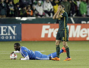 Photo - Portland Timbers midfielder Diego Valeri, right, reacts after fouling Philadelphia Union midfielder Maurice Edu during the first half of an MLS soccer game in Portland, Ore., Saturday, March 8, 2014. (AP Photo/Don Ryan)