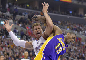 Photo - Los Angeles Clippers forward Blake Griffin, left, and Los Angeles Lakers forward Metta World Peace tangle during the first half of their NBA basketball game, Friday, Jan. 4, 2013, in Los Angeles.  (AP Photo/Mark J. Terrill)
