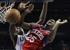 Photo - Philadelphia 76ers' Elliot Williams, front, is fouled by Charlotte Bobcats' Bismack Biyombo, back, during the first half of an NBA basketball game in Charlotte, N.C., Friday, Dec. 6, 2013. (AP Photo/Chuck Burton)