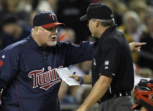Photo - Minnesota Twins manager Ron Gardenhire, left, argues with home plate umpire Tim Timmons against the Detroit Tigers in the sixth inning of a major league baseball game in Detroit, Friday, Sept. 24, 2010. Gardenhire was ejected from the game. (AP Photo/Paul Sancya) ORG XMIT: MIPS112