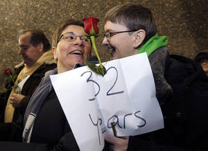 Photo - Melody Platt, left, and her partner Beratta Gomillion wait among the first couples in line to be issued a marriage license to a same-sex couple, Wednesday, Dec. 5, 2012, in Seattle. King County Executive Dow Constantine was to began issuing the licenses just after midnight, Thursday, Dec. 6, immediately upon certification of the November election that passed Referendum 74 allowing same-sex couples to wed. The couple are planning on getting married on their 32nd anniversary, Monday Dec. 12. (AP Photo/Elaine Thompson)