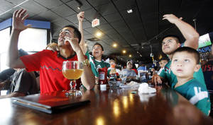 Photo -  Roberto Hernandez, left, Oscar Chavez, middle left, Edgar Chavez, middle right, and Brayan Chavez, right, cheer during a World Cup watch party for the Brazil versus Mexico game Tuesday at Medio Tiempo Sports Cantina and Grill. Photos by K.T. King, The Oklahoman  <strong>KT King</strong>