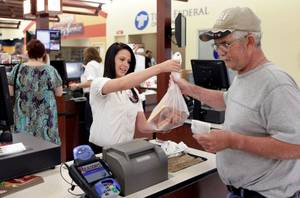 Photo - Cashier Sarah Vlack assists David Tilley at the new Reasor's store in Sand Springs.  Photo by MIKE SIMONS, Tulsa World