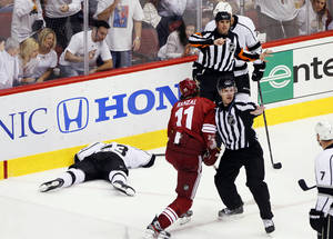 Photo -   Los Angeles Kings right wing Dustin Brown lies on the ice after being hit by Phoenix Coyotes center Martin Hanzal (11) during the third period of Game 2 of the NHL hockey Stanley Cup Western Conference finals, Tuesday, May 15, 2012, in Glendale, Ariz. The Kings won 4-0. (AP Photo/Matt York)