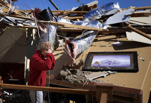 Photo -   Carole Beckett reacts as she sorts through belongings at her home after a tornado moved through Woodward, Okla., Sunday, April 15, 2012. Residents of several states scoured through the wreckage of battered homes and businesses after dozens of tornadoes blitzed the Midwest and Plains Saturday night. (AP Photo/The Oklahoman, Bryan Terry)
