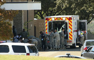 Photo - Wounded soldiers are prepared for transport Nov. 5, 2009, in waiting ambulances outside Fort Hood's Soldier Readiness Processing Center in Fort Hood, Texas. Public works officials announced plans Tuesday to raze the structure that's part of the Soldier Readiness Processing Center. AP FILE PHOTO