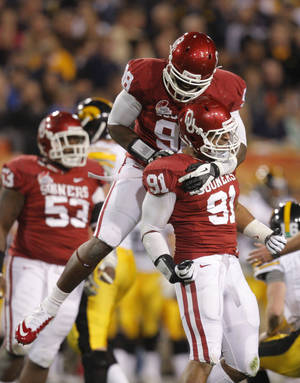 photo - CELEBRATION: Oklahom's Chuka Ndulue (98) and R.J. Washington (91) celebrate a sack during the Insight Bowl college football game between the University of Oklahoma (OU) Sooners and the Iowa Hawkeyes at Sun Devil Stadium in Tempe, Ariz., Friday, Dec. 30, 2011. Photo by Sarah Phipps, The Oklahoman