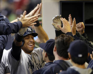 Photo - New York Yankees' Yangervis Solarte is congratulated in the dugout after his three-run home run against the Milwaukee Brewers in the fourth inning of a baseball game Friday, May 9, 2014, in Milwaukee. (AP Photo/Jeffrey Phelps)