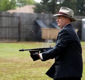 Photo - C.W. Moss fires a 1928 Thompson submachine gun as he re-enacts a 1933 bank robbery during last year's  Living History Days at the Chisholm Trail Museum in Kingfisher. Photo by Bryan Terry, The Oklahoman Archives <strong>BRYAN TERRY - THE OKLAHOMAN</strong>