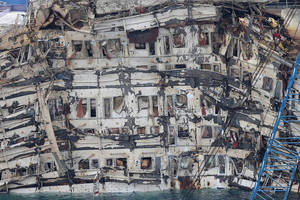 "Photo - A detail of the previously submerged side of the Costa Concordia is seen after it was lifted upright, on the Tuscan Island of Giglio, Italy, Tuesday, Sept. 17, 2013. The crippled cruise ship was pulled completely upright early Tuesday after a complicated, 19-hour operation to wrench it from its side where it capsized last year off Tuscany, with officials declaring it a ""perfect"" end to a daring and unprecedented engineering feat. (AP Photo/Andrea Sinibaldi, Lapresse) ITALY OUT"