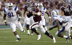 Photo -   Texas A&M quarterback Johnny Manziel (2) runs for a touchdown as South Carolina State's Kimario McFadden (7) and Curtis Hill (91) try to tackle him during the second quarter of an NCAA college football game on Saturday, Sept. 22, 2012, in College Station, Texas. (AP Photo/David J. Phillip)