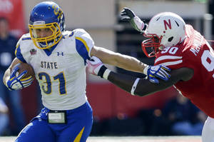 Photo - South Dakota State running back Zach Zenner (31) runs past the tackle of Nebraska defensive end Greg McMullen (90) in the first half of an NCAA college football game in Lincoln, Neb., Saturday, Sept. 21, 2013. (AP Photo/Nati Harnik)