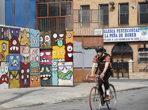 Photo - A cyclist pedals by a a street art mural and a storefront church, Tuesday, April 22, 2014, in Brooklyn's Bushwick neighborhood in New York. The neighborhood, once considered dangerous, is beginning to attract tourists and hipsters. (AP Photo/Kathy Willens)