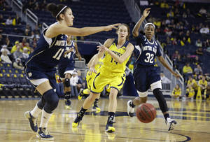 Photo - Michigan guard Nicole Elmblad (14) passes the ball while defended by Notre Dame forward Natalie Achonwa (11) and guard Jewell Loyd (32) during the first half of an NCAA women's college basketball game in Ann Arbor, Mich., Saturday, Dec. 14, 2013. (AP Photo/Carlos Osorio)