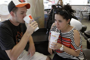 Photo - FILE - In this Sept. 13, 2012 photo, Luke Husemann, and Christina Nunez, of Baltimore, sip on extra-large soft drinks at a McDonald's restaurant in New York. The city defended its groundbreaking size limit on sugary drinks Wednesday, Jan. 23, 2013, as an imperfect but meaningful rein on obesity, while critics said it would hurt small and minority-owned businesses while doing little to help health. (AP Photo/Kathy Willens, File)