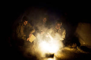 Photo - Syrian men heat a fire to boil water near their tent at a refugee camp near the Turkish border, in Azaz, Syria, Sunday, Dec. 9, 2012. (AP Photo/Manu Brabo)