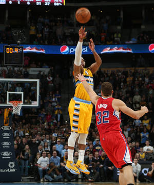 Photo - Denver Nuggets guard Randy Foye, back, shoots a 3-point basket over Los Angeles Clippers forward Blake Griffin with nine-tenths of a second remaining in the fourth quarter of the Nuggets' 116-115 victory in an NBA basketball game in Denver, Monday, Feb. 3, 2014. (AP Photo/David Zalubowski)