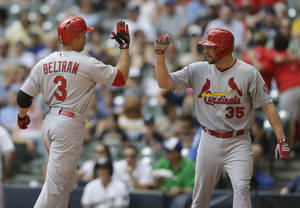 Photo - St. Louis Cardinals' Jake Westbrook(35) gives a high-five to Carlos Beltran after his two run home run against the Milwaukee Brewers during the second inning of a baseball game Wednesday, Aug. 21, 2013, in Milwaukee. (AP Photo/Jeffrey Phelps)