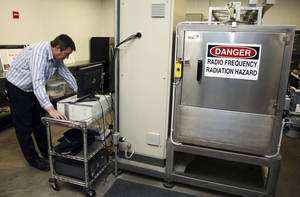 Photo - Andreas Neuber, an electrical engineering professor at Texas Tech University, monitors a high-powered microwave at Microzap Inc., in Lubbock, Texas.  AP Photo