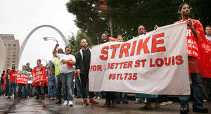Photo - Demonstrators walk July 30 through downtown St. Louis to demand a better minimum wage. On Thursday organizers say thousands of workers are set to stage walkouts in at least 50 cities around the country. AP Photo