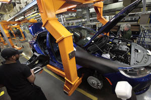 Photo - In this March 14, 2014 photo, an assembly line worker builds a 2015 Chrysler 200 automobile at the Sterling Heights Assembly Plant in Sterling Heights, Mich. Chrysler Group LLC reports quarterly earnings on Monday, May 12, 2014. (AP Photo/Paul Sancya)