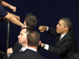Photo - President Barack Obama acknowledges the crowd as he exchanges fist bumps with the audience after speaking at Hyde Park Academy, Thursday, Feb. 14, 2013, in Chicago. (AP Photo/M. Spencer Green)
