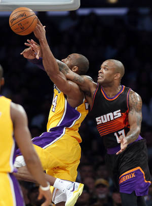 photo - Phoenix Suns' P.J. Tucker, right, fouls Los Angeles Lakers' Kobe Bryant during the first half of an NBA basketball game on Tuesday, February 12, 2013, in Los Angeles. (AP Photo/Danny Moloshok)