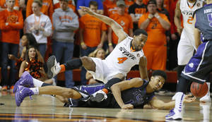 Photo - Oklahoma State's Brian Williams (4) leaps for the ball beside TCU's Karviar Shepherd (1) during an NCAA college basketball game between Oklahoma State University (OSU) and TCU at Gallagher-Iba Arena in Stillwater, Okla., Wednesday, Jan. 15, 2014.  Photo by Bryan Terry, The Oklahoman