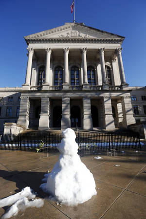 Photo - A snowman melts on the steps of the Georgia State Capitol building Thursday, Feb. 13, 2014, in Atlanta. As crews worked to restore power to hundreds of thousands of Georgians, forecasters hoped warmer temperatures and sunshine would melt ice-coated roads across the state. (AP Photo/John Bazemore)