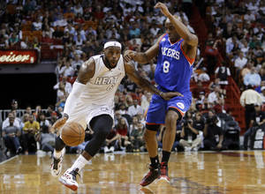 Photo - Miami Heat's LeBron James (6) moves down the court past Philadelphia 76ers' Damien Wilkins (8) in the first half of an NBA basketball game, Saturday, April 6, 2013, in Miami. (AP Photo/Lynne Sladky)