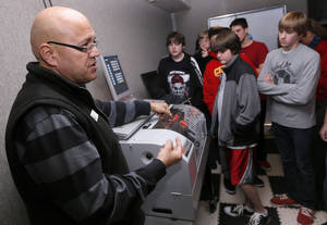 Photo - Steve Marquardt, left, industrial coordinator for Pioneer Technology Center, talks with students from Alcott Middle School.