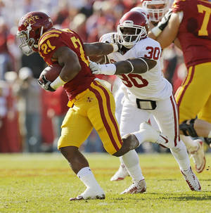 Photo - Oklahoma's Javon Harris (30) tries to stop Iowa State's Shontrelle Johnson (21) during a college football game between the University of Oklahoma (OU) and Iowa State University (ISU) at Jack Trice Stadium in Ames, Iowa, Saturday, Nov. 3, 2012. Photo by Nate Billings, The Oklahoman