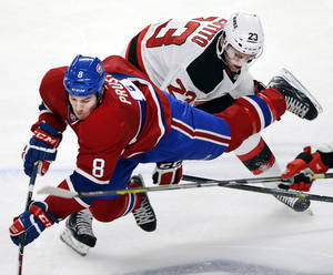 Photo - Montreal Canadiens right wing Brandon Prust (8) is upended by New Jersey Devils center Tim Sestito during the first period of an NHL hockey game in Montreal on Monday, Dec. 2, 2013. (AP Photo/The Canadian Press, Ryan Remiorz)