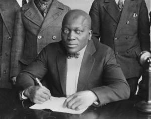 Photo - Boxer Jack Johnson is shown signing contracts in this undated photo. Relatives and hometown supporters of boxing's first black heavyweight champion are turning to YouTube to convince the president to posthumously pardon him of a 1913 conviction for accompanying a white woman across state lines, Tuesday, April 2, 2013. (AP Photo/file)