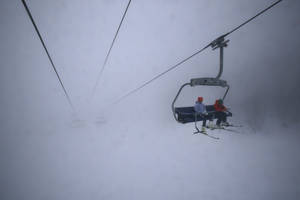 Photo - Skiers take a chair lift up the mountain in heavy fog near the alpine skiing training slopes at the Sochi 2014 Winter Olympics, Monday, Feb. 17, 2014, in Krasnaya Polyana, Russia. (AP Photo/Christophe Ena)
