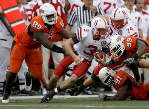 photo - Nebraska's Taylor Martinez avoids OSU's Nigel Nicholas, left, Ugo Chinasa, and Richetti Jones, right, during the college football game between the Oklahoma State Cowboys (OSU) and the Nebraska Huskers (NU) at Boone Pickens Stadium in Stillwater, Okla., Saturday, Oct. 23, 2010. Photo by Bryan Terry, The Oklahoman