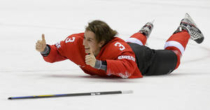 Photo - Sarah Forster of Switzerland (3) slides on the ice while celebrating Switzerland's 4-3 win over Sweden in the women's bronze medal ice hockey game at the 2014 Winter Olympics, Thursday, Feb. 20, 2014, in Sochi, Russia. (AP Photo/Matt Slocum)