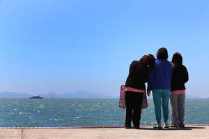 Photo - Relatives of a passenger aboard the sunken Sewol ferry look toward the sea at a port in Jindo, South Korea, Wednesday, April 30, 2014. South Korea's president apologized Tuesday for the government's inept initial response to a deadly ferry sinking as divers fought strong currents in their search for nearly 100 passengers still missing nearly two weeks after the accident.(AP Photo/Yonhap)  KOREA OUT