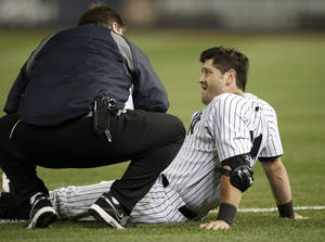Photo - A Yankees trainer, left, talks to New York Yankees Francisco Cervelli who was injured on a fourth-inning force out play that was overturned in a baseball game against the Boston Red Sox at Yankee Stadium in New York, Sunday, April 13, 2014.  The Yankees Brian McCann scored on the play, but Cervelli left the game.  (AP Photo/Kathy Willens)