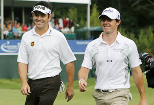 Photo -   Louis Oosthuizen, left, of South Africa, and Rory McIlroy, of Northern Ireland, leave the 18th green after finishing the third round of the Deutsche Bank Championship PGA golf tournament at TPC Boston in Norton, Mass., Sunday, Sept. 2, 2012. (AP Photo/Michael Dwyer)